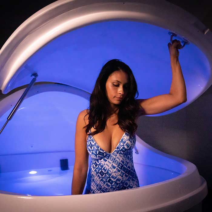 woman getting into sensory deprivation chamber